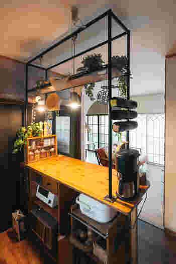 カウンター上部に設置された天井まで届く大きなフレーム。高い位置に金網を設け、ディスプレイも兼ねて収納。金網なので吊るす収納も多彩。 高い位置なので目線を妨げず圧迫感もありません。