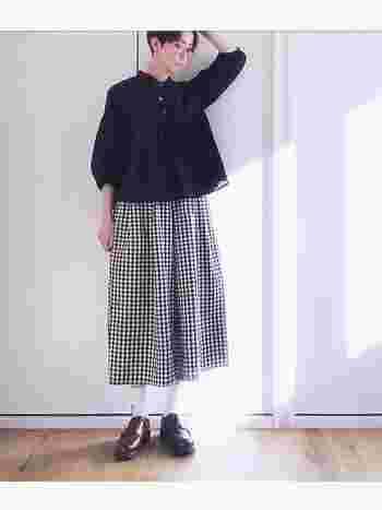 大人ならではの着こなしが光るギンガムチェックのフレアスカートには優しい素材の黒いブラウスを合わせて優等生風にコーディネート。少し弛ませた靴下が足首を細く見せてくれます。