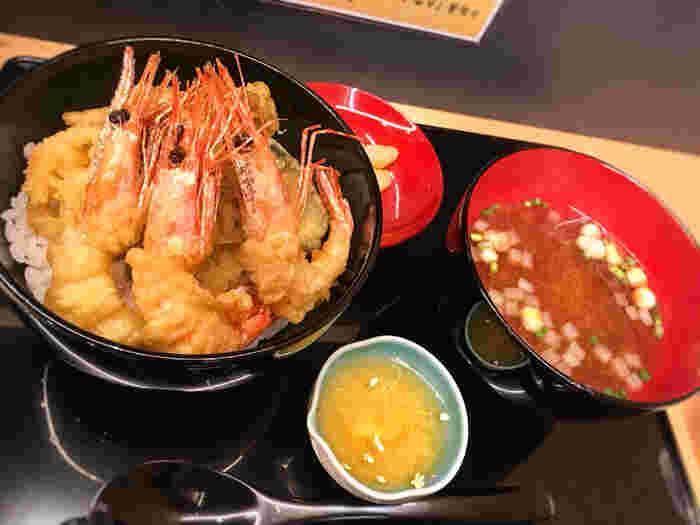"""""""加賀百万石""""の綺羅びやかさが伝わるのは《加賀百万石天丼》。揚げたての海老と野菜の天ぷらが贅沢に盛り込まれた天丼です。 イートインのランチメニューはこの他に、加賀の食材を用いた《週替り丼》が数種類用意されています。"""
