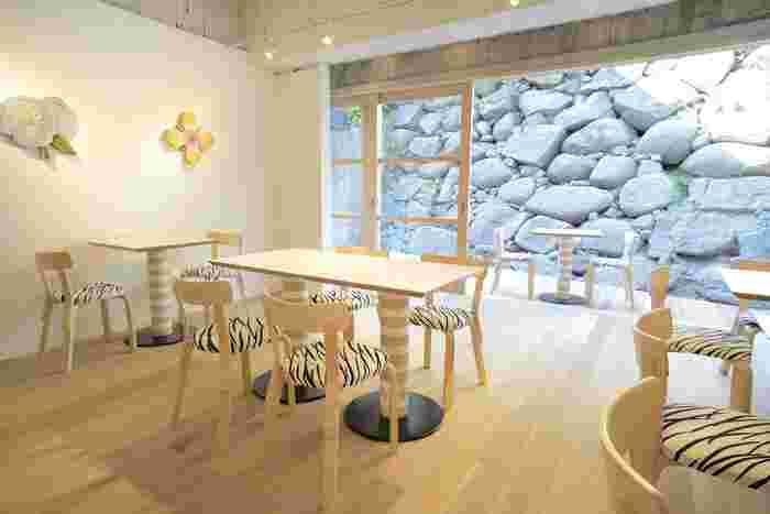 """愛媛県美術館から10分ほど歩いたところに、石本さんがプロデュースしたギャラリー&茶房「MUSTAKIVI(ムスタキビ)」があり、こちらも立ち寄りたいスポット。本展会期中は連動企画として、石本さんの""""故郷""""をテーマにした作品展示を実施しています。  石本さんが手がけたマリメッコのテキスタイル、陶板の花が彩る、北欧インテリアでコーディネートされた空間です。ナチュラルな雰囲気で、居心地がいいですね。"""
