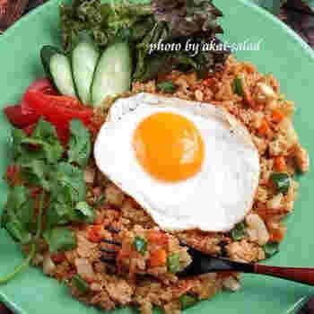 定番のインドネシア料理、ナシゴレン。いつもの焼き飯に一手間加えて作る、簡単レシピのご紹介です。鶏ひき肉や人参などの野菜を加えて、スイートチリソースとカレー粉を一緒に炒めます。そして、合わせダレとご飯を加えて一煮立ち。半熟目玉焼き、パクチー、トマトなどをトッピングすれば、彩り豊かなインドネシア料理の完成です。