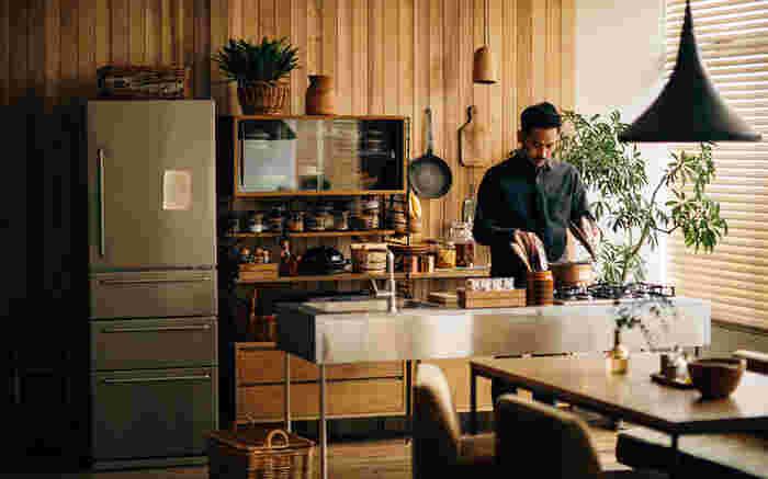 ステンレスのアイランドキッチンの前に配置。キッチン自体が無駄がなくスッキリとした印象ですね。ヴィンテージ感ただよう、人を招きたくなるようなオシャレなインテリアです。ダイニングテーブルからの視線も届きやすく、家事動線もバッチリですね。