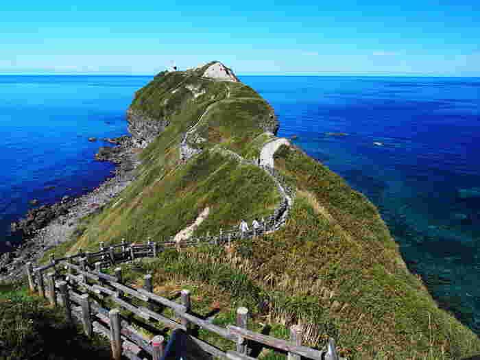 古くは女人禁制の修行の地だったという神威岬(かむいみさき)。遊歩道を歩いて先端まで歩くことができ、周囲には積丹ブルーと呼ばれる青く美しい海が眼下に広がります。