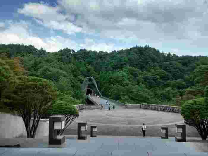 信楽町の中心部から離れた山間部に位置するこの美術館は、「桃源郷」をモチーフにして建設されています。周囲の美しい山岳風景と調和したトンネルのような入り口を通り抜けると、忽然と美術館の建物が現れ、モチーフそのまま、桃源郷を訪れたような気分を楽しむことができます。