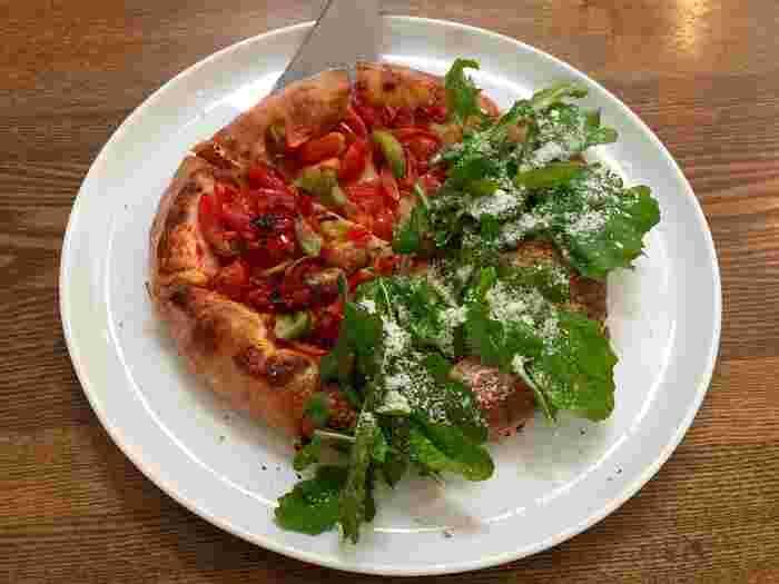 予約するのが難しいことでも知られているこちらのお店、実は代々木上原や京都にも姉妹店がある人気店の本店なんです。目にも鮮やかな赤と緑が美しい「トマトとルッコラのハーフ&ハーフ」のピザは、フレッシュで風味豊か。