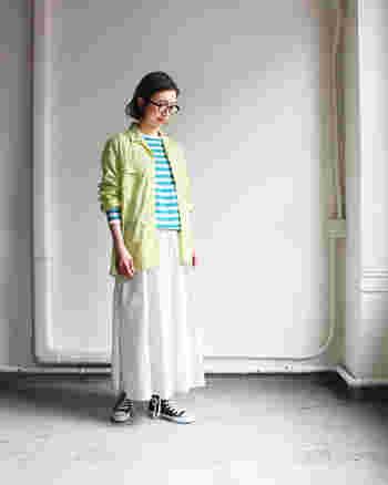 エメラルドブルーのボーダートップスに、グリーン系のシャツをレイヤードした着こなし。足元は白のフレアスカートで、とことん爽やかにまとめています。