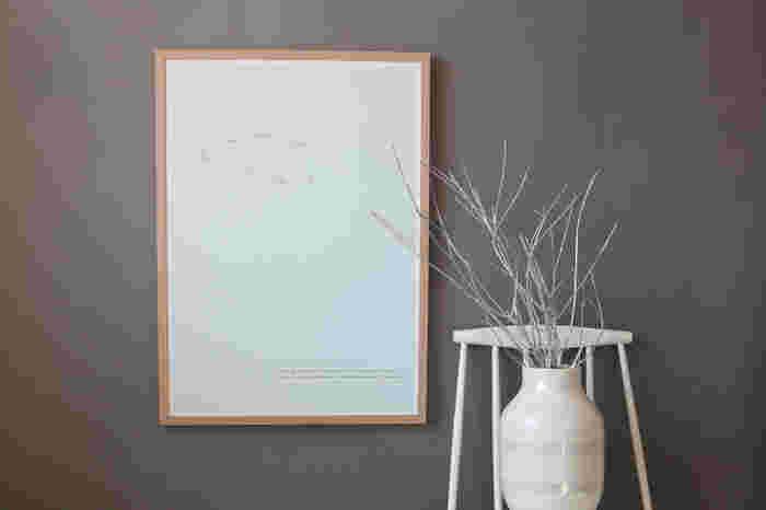 低めの位置に大きなポスターを飾ると、普段とは違う視線の流れができます。シンプルなスツールと花瓶を一緒にアレンジすることでよりアーティスティックな空間に仕上げています。