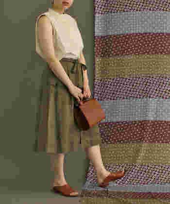 カーキのスカートにホワイトのブラウスを合わせ、ほんのりフェミニンな印象に。レザーのバッグとサンダルで、シンプルな着こなしに深みを足し算して。