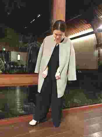 黒のきれいめオールインワンに、上質なグレーのカシミアコートを羽織ったパーティースタイル。ノーカラーが上品な印象で、白のパンプスやイアリングで大人の華やかさを加えています。