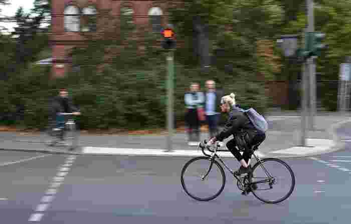 颯爽と街を行く自転車女性。飾り気のないモノトーンコーデが逆にハッとするほど新鮮です。