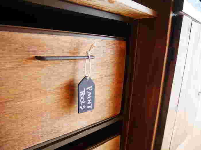 残ったベニヤ板でタグを作って吊るすアイデアも素敵。少なめの材料でナチュラルテイストの棚へと生まれ変わりますよ。