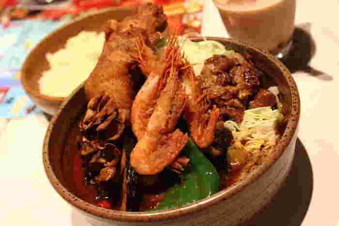 スープカレーの楽しみのひとつは、自分で好みのトッピングを選べること。こちらは北海道産牛すじ煮込みに、蒸しキャベツ、プレミアム舞茸、オクラ、チキン、海老の唐揚げ…スープが見えないほど豪華なトッピングです!