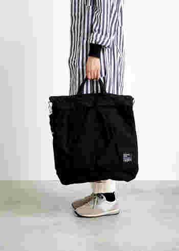 アメリカ軍が使用していたヘルメットバッグのデザインがベースになっていて、大きな二つのポケットをフロントに配置しているのが特徴のアイテムです。シンプルな黒の大きめトートのよう見えるので、どんなファッションスタイルにも合わせやすいのが魅力。