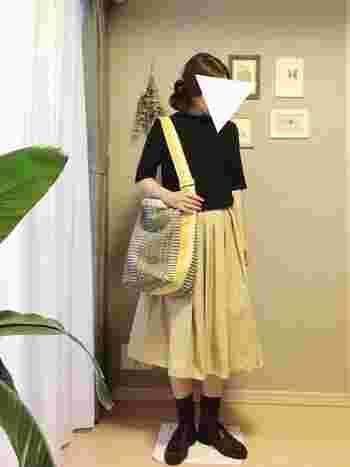 ハイネックリブTとふんわりスカートのフェミニンなコーディネートは、ヨハンナグリクセンのバッグを主役に。