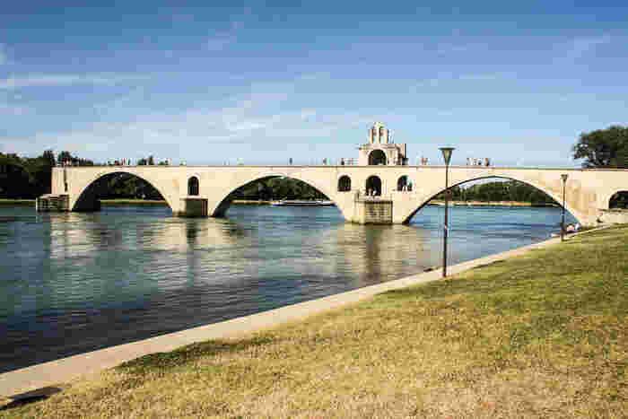 童謡「アヴィニョンの橋」で世界中にその名が知れ渡っているアヴィニョン橋ことサン・ベネゼ橋は、1177年から8年の歳月をかけて建築されたものです。現在は、礼拝堂と4個のアーチを残すだけの小さな橋となっていますが、橋が創建された当時は、22個のアーチを持ち、ローヌ川対岸のヴィルヌーヴ・レザヴィニョン街にあるフィリップ美男王の塔まで届くほどの大きな橋だったと伝えられています。