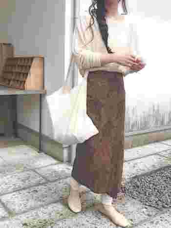 ペイズリー柄が大人っぽい雰囲気のタイトなロングスカートには、少したるませた白系レギンスを合わせて。スカート以外はオフホワイトで揃えるとまとまり感が出て◎