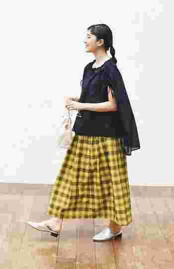 イエローベースのチェック柄スカートに、黒の無地トップスを合わせたコーディネートです。黒はどんなトップスに合わせても大人っぽくキマる一枚ですが、さらにスカートにも黒のラインが入っているので、まとまったスタイリングに。足元はシルバーシューズで、ワンアクセントをプラス。