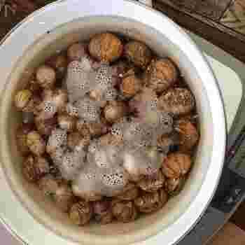【2】すべて剥き終わったら鍋に栗が浸るくらいの水を入れ重曹を加え火にかけます。鍋の中の水が黒っぽく濁ってきたら火を止めお湯を8割ほど捨て、栗が浸かり手を入れられるぐらいの温度になるまで水を足し、渋(筋)を取って水かぬるま湯を張ったボウルに入れておきます。  【3】全て渋を取り終えたら再度水かぬるま湯を入れて火にかけ、お鍋が煮立つ前・フツフツと沸いてきたぐらいで火を止め、【2】の工程を2度繰り返します。