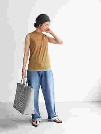 洗練された雰囲気漂うノースリーブニット×デニムの大人カジュアル。裾からさりげなく覗かせたグレーのインナーが着こなしのアクセントに。ヘアターバンやバッグなど、夏らしい小物使いもおしゃれな雰囲気です。