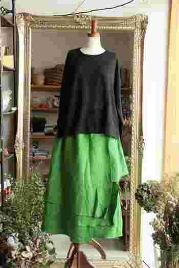スカートの艶やかさが引き立つよう、トップスはブラックにして小気味よいカラーバランスに。布が幾重にも重なったティアードデザインが、着こなしに立体感を生んでいます。