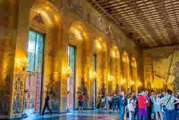 こちらが、ダンスパーティーが行われる黄金の間。  その名にぴったりな、ゴールドと温かな光がきらめく美しい空間ですね。