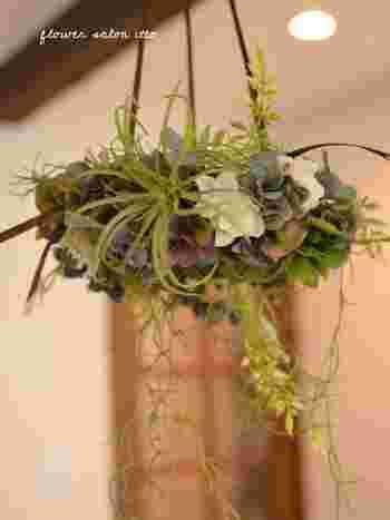 こちらは吊るして楽しむフライングリース。フェイクグリーンをベースに造花を加えて華やかに。ナチュラルなシャンデリアのように楽しむことができます。