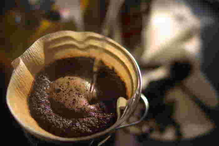 """まずは通常のホットコーヒーを淹れます。美味しく淹れるコツは、コーヒー豆を""""蒸らす""""ことです。  ①ドリッパーにペーパーフィルターをセットし、分量のコーヒー粉を入れる。 ②蒸らしのお湯を注ぐ。 コーヒー粉の真ん中に、コーヒー粉全体に水分がまわる程度のお湯を静かに注ぎます。 ③20~30秒程度蒸らす。 粉全体にお湯がまわってくると粉が膨らみます。膨らみを上手に作ると、豆の成分がコーヒーによく抽出されますよ。 ④淹れるための湯を注ぐ。 蒸らしが終わったら、のの字を書くように静かに注ぎます。ムラなく抽出されるよう一定のスピードで注ぐのがポイントです。粉の膨らみにあわせ2~3度にわけて淹れましょう。"""