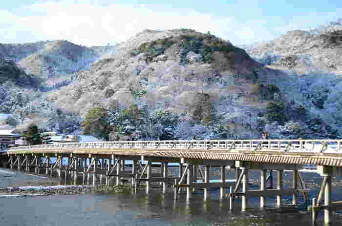 京都嵐山のシンボルともいえる「渡月橋」。大堰川に架かる橋で、月が渡るさまに似ているという事から亀山天皇が命名したと言われています。四季折々の景色が楽しめる人気のスポットですが、桜や紅葉の時期に負けず劣らず雪化粧も華麗で何とも言えない美しさです。