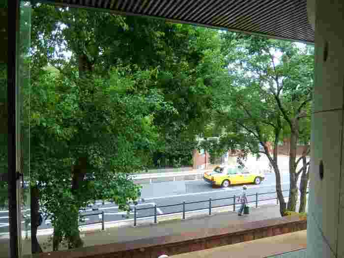 """けれども実際は、その様なイメージに反し、緑が多く、自然豊か。総面積は、約53万㎡にも及び、南部に位置する「不忍池(しのばずのいけ)」、西部の「東京藝術大学」やその周辺地域も園内に含む、広大なる""""都市公園""""です。  【美術館や陳列館、学食やアートプラザ(後述)等、東京藝大構内の一部の建物は、学生以外の一般の人でも見学可能。守衛所でその旨伝えれば構内へ入れる。   (画像は、大学美術館内「ミュージアムカフェ」からの眺め。右奥は、東京藝術大学音楽学部の正門。東京藝術大学大学美術館(入館有料)は、卒業生や教員らの寄贈作品を所蔵する美術館で、その作品群は、近現代の美術史を語る上で欠くことのできない貴重なものとなっている。企画展やコレクション展、学生の作品展などが開催される。)】"""