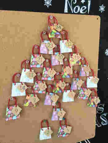ミニ手提げ袋をコルクボードなどにピン止め。カレンダーのように四角く貼ってもいいですが、ツリー型になるように貼るとクリスマス感が出ますね。