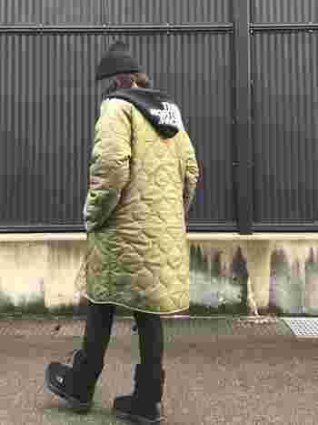 後ろ姿にポイントを作れるのもパーカー×コートの魅力。カーキのキルティングコート以外を黒で統一することで、ノースフェイスのロゴが際立っています。