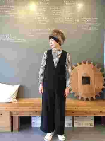 深Vネックの滑らかな生地の黒サロペットにストライプのシャツを合わせたマニッシュコーデ。ふわふわの帽子を合わせて、より可愛らしく楽しい、冬のスタイリングです。