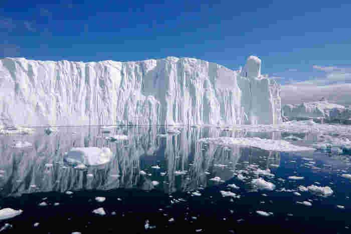 デンマーク領のグリーンランドにあるイルリサット・ アイスフィヨルドは、島の約8割が氷で覆われている島です。垂直に切り立った氷の壁、紺碧の海に浮かぶ大小の氷片、波一つない静かな海面、抜けるような青空が融和した見事な景観から、イルリサット・アイスフィヨルドは、世界遺産に登録されています。