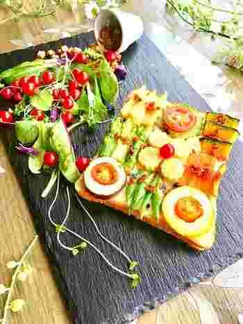 食パンにスライスチーズを敷き、レンジで軽く加熱した野菜を配置し、ベーコンビッツを散らします。あとは、オーブントースターで焼くだけ。なすやズッキーニの真ん中にはプチトマトを。下にチーズが敷いてあるので、野菜がずれません。