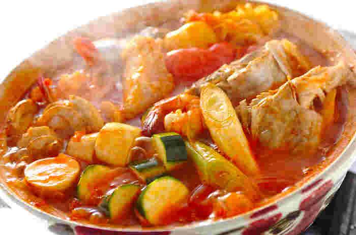 トマトの水煮缶とトマトピューレのW使いの「トマト鍋」。野菜と魚介類のダシがしみでたスープはしみじみおいしいです。シメは、パスタやご飯をいれてリゾット風にするのがおすすめ。薬味のクリームチーズがいい味わいです。