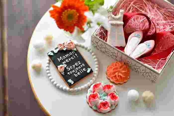 """「誰かにプレゼントしたくなるお菓子」がコンセプトの、大阪・堀江にあるお菓子屋さん「パティスリーブーケ」。パリが大好きな店主、高橋美絵子さんがつくる""""母の日アイシングクッキー""""が今年も登場です!  繊細なお花、可愛らしいワンピースと靴…。ひとつひとつ丁寧に手作業でつくられたクッキーに心が躍ります。黒板クッキーには「お母さんありがとう。いつまでもキレイでいてね」というフランス語のメッセージが♪賞味期限は1ヶ月程あるので、最初のうちは飾って楽しんでもらうのもいいですね。"""