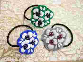 お出かけ時はもちろん、さっと髪をまとめたい家事の時など、「ヘアゴム」ってなにかと重宝しますよね。お花の刺繍をしたカラーフェルトを取り付ければ、お出かけファッションに合わせたくなるアクセサリーに変身。 こちらは刺繍でつくったお花の中心に、フェルトと同色系のビーズをたくさんあしらっていて、かわいらしくも凛とした美しさを感じます。