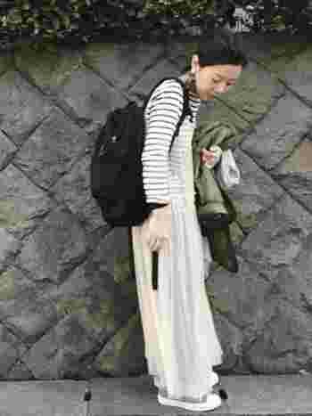 ボーダーTシャツとデニムの上から白のシフォンワンピースをレイヤードして、黒リュックで引き締めたスタイル。スタンダードアイテムに今風の柔らかいニュアンスをプラスした奥行きのあるコーディネートです。