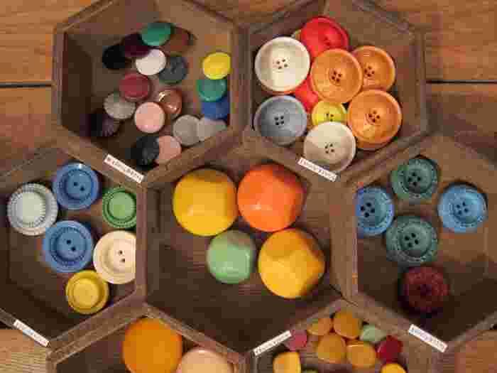 こちらはコロンとした丸みのあるフォルムが愛らしいボタン。色・形・大きさが様々なので、生地に合わせるのはもちろん、アクセサリーとして組み合わせてイヤリングやネックレスにするのもおすすめです。POPなカラーのボタンは、古着のアウターのボタンにアクセントとして使用したり、逆に渋みのあるカラーのボタンは帽子に付けてコーデに馴染ませてみたりと愉しみ方も無限大です。