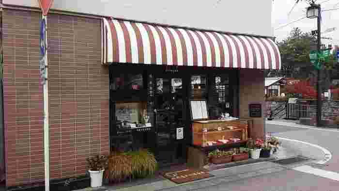 ショーケースに並んだ昔懐かしい洋食が食欲をそそる食堂です。ストライプの屋根や格子のドアも雰囲気があります。