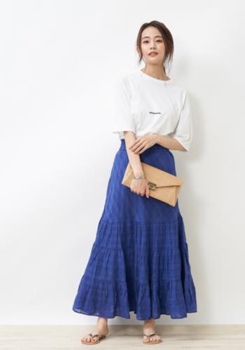 白Tにブルーのチェックスカートを合わせた大人カジュアルスタイル。ホワイト×ブルーは爽やかな雰囲気を演出できる、夏の鉄板コンビです。動くたびにふわっと揺れるティアード風のスカートは、カジュアルなコーディネートでも女性らしさを確保できます。クラッチバッグでこなれ感をプラスするのもアリ。