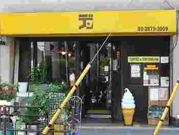 「デン」は鶯谷駅南口から歩いて約5分。個性的なフォントが可愛いイエローの看板が目印です。店前には、ソフトクリームの置物も。