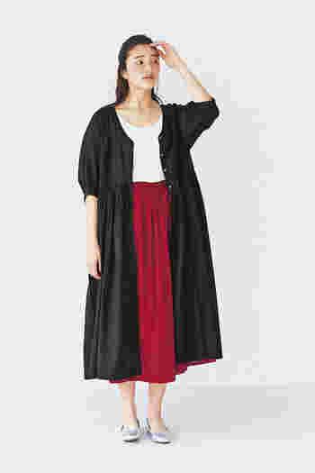 たっぷりとギャザーの入った赤スカートは、女性らしさをグッと高めてくれるアイテム。白トップスと黒の羽織をプラスして、ベーシックで上品なコーディネートに仕上げています。