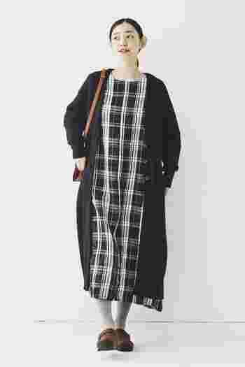 モノトーンのチェック柄ワンピースに、黒のカーディガンを合わせたナチュラルなスタイリングです。薄いグレーのタイツとブラウンのシューズ・バッグで、程よく上品な印象を与える着こなしに。