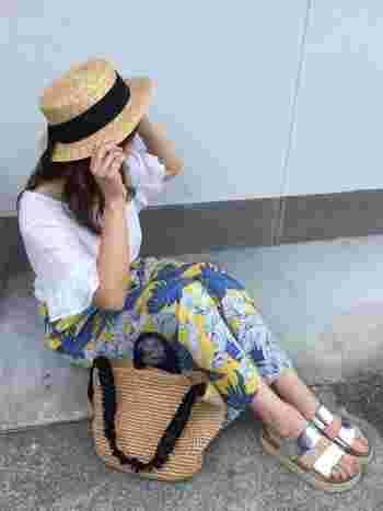 トロピカルな花柄のワイドパンツは白のトップスと合わせて、夏のリゾート風スタイルに。天然素材のハットやバッグが、ナチュラルな印象をプラスしてくれます。