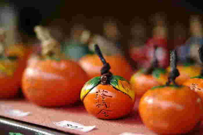 """「おかもと勇楽」は、落柿舎傍にある嵯峨土面・土鈴のお店。店に並ぶのは、湯呑みや茶碗、柿の土鈴の数々。愛情込めて作る土鈴は、実に素朴で温か。嵯峨の散策の記念におすすめのお土産です。カラコロと鳴る音色も、朗らかで温か。 【画像は、落柿舎にちなんだ""""柿の土鈴""""。店先ではご主人が土鈴づくりの実演をしています。】"""