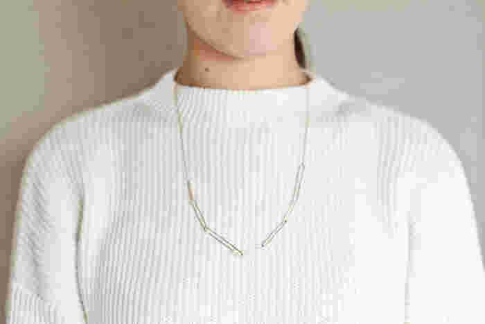 ロングネックレスは首元の詰まったトップスによく合います。控えめな光沢のゴールドなので、シンプルなニットのアクセントにもぴったり!ユニークなデザインが際立ちますね。