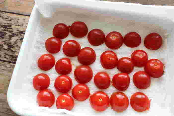 半分に切ったトマトに塩をふります。カット面に果肉が見えている方が水分が抜けやすいので、ヘタ部分を上にして横半分に切ると良いでしょう。水分が出たら、天日に干していきます。