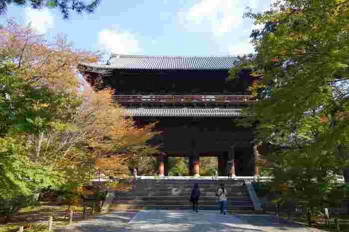 """日本三大門の一つに数えられる「南禅寺三門」は、五間三戸二階二重門、入母屋造、本瓦葺きで""""天下竜門""""とも呼ばれ、高さ22mにも及びます。  現在の「三門」は、藤堂高虎が""""大阪夏の陣""""に倒れた家来の菩提を弔うために再建したものです。 「五鳳楼」と呼ばれる楼上には、内陣、須弥壇があり、本尊『宝蔵釈迦坐像』を中心として月蓋長者や善財童士等が並ぶ他、本光国師、徳川家康、藤堂高虎の像、一門の重臣の位牌が安置されています。【11月初旬の三門】"""