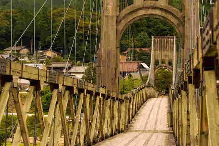 木曽川に架かる全長247メートルの木橋、桃介橋は1922年に完成した吊橋です。木製補剛桁を使った吊橋としては、日本有数の大きな橋で、木曽川と融和した壮観な美しさを誇っています。